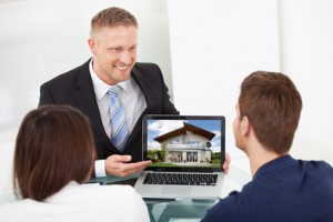 Advisor Showing House Picture To Couple On Laptop