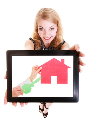 Real estate agent showing paper house on tablet.